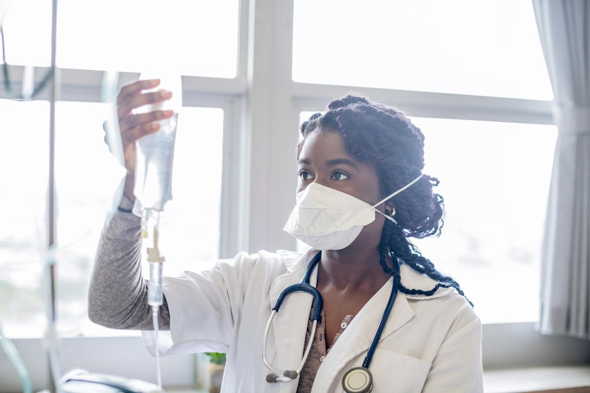 A doctor is seen in a hospital with an IV drip.