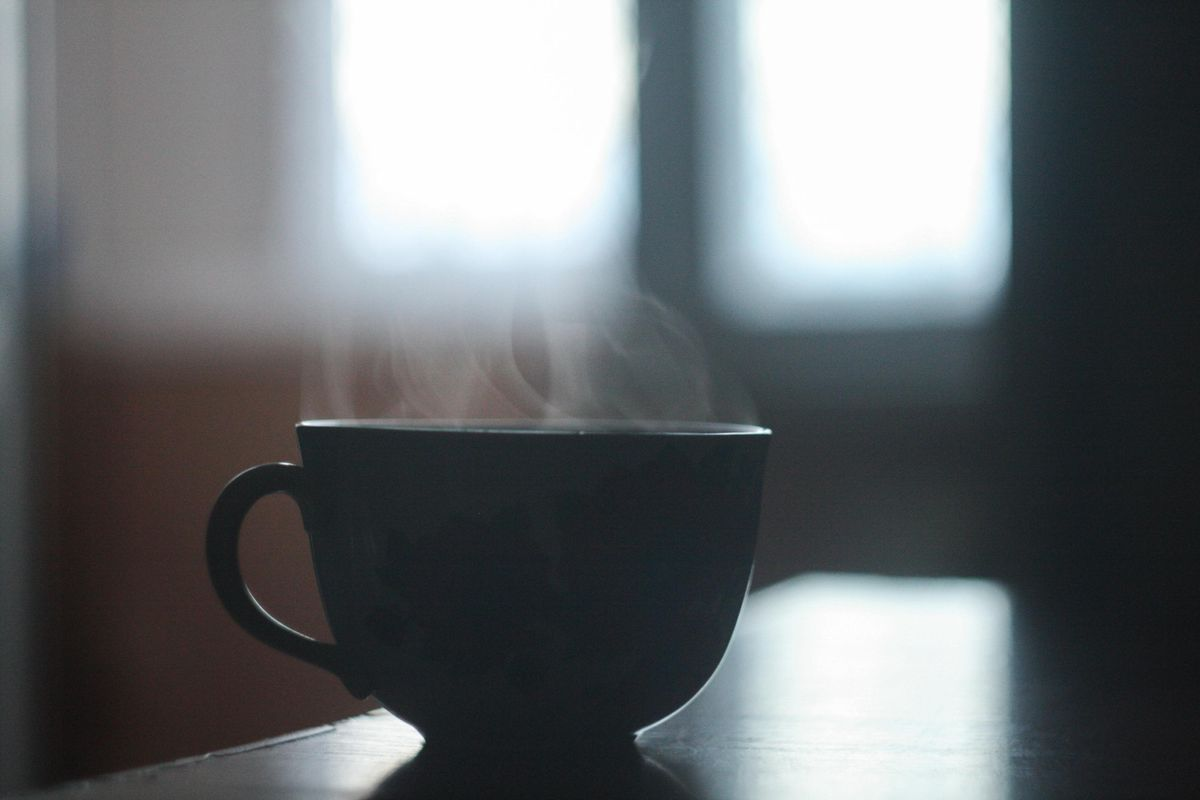 A mug of coffee sits on a table.