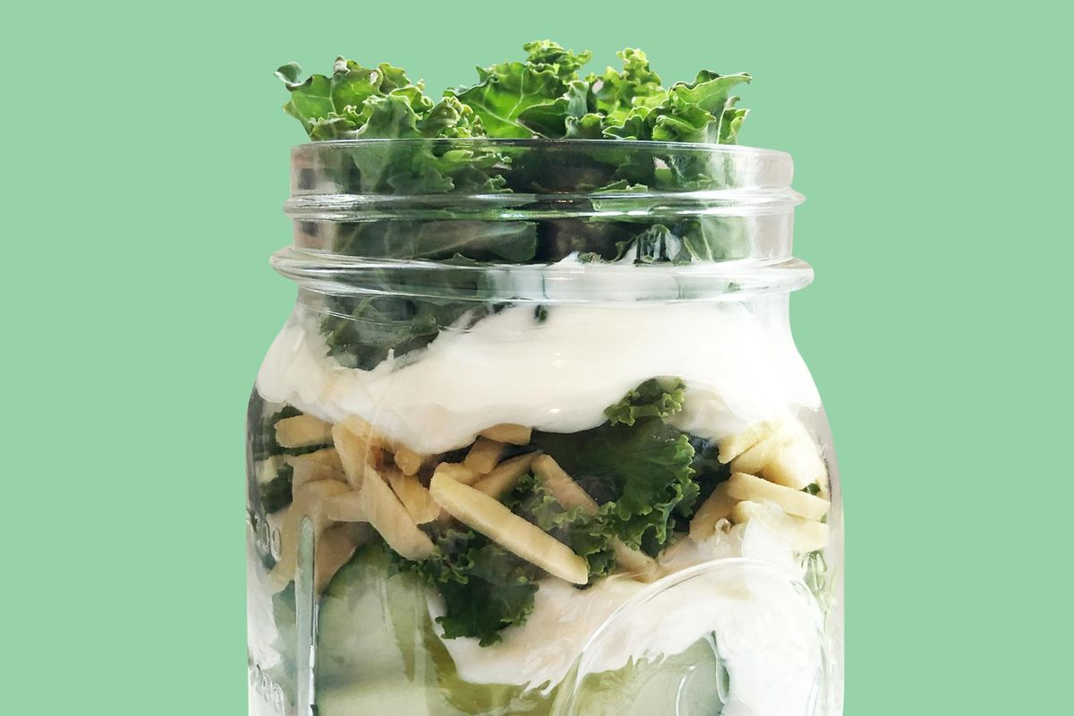 A jar salad has lettuce and veggies inside.