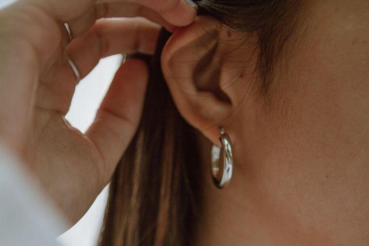 A woman tucks her hair behind her ear.