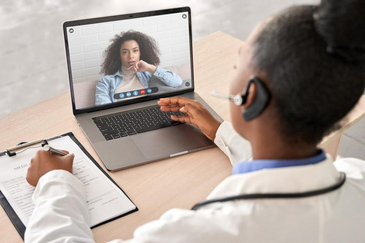 Woman talking to doctor on computer