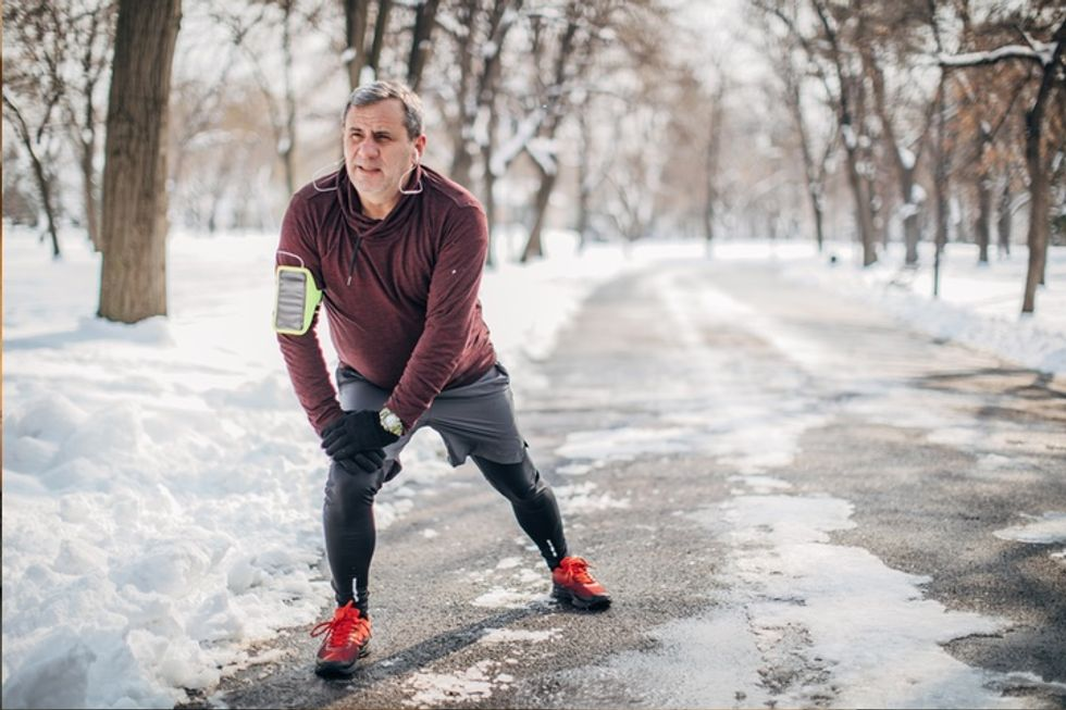Photo of a white man stretching before a run outside. Snow is on the ground.